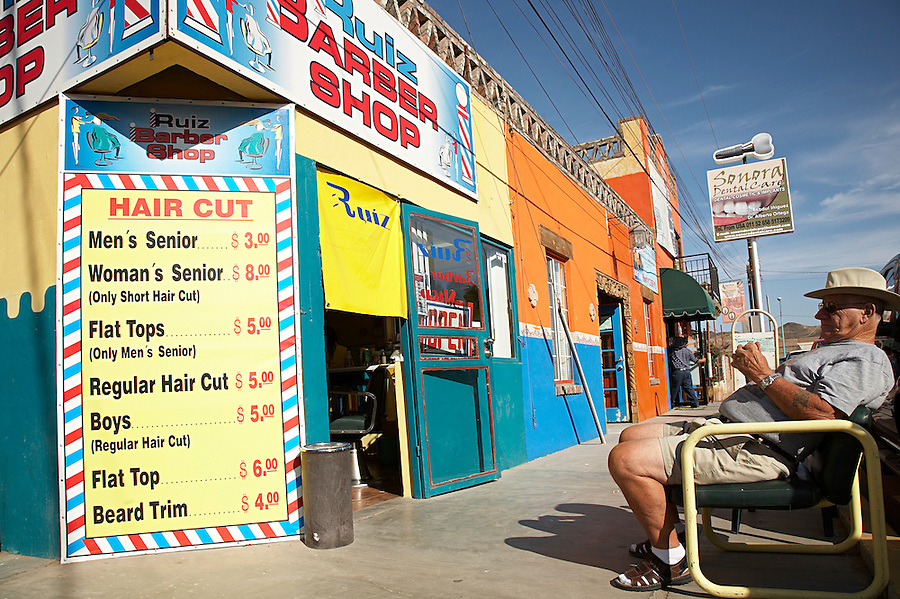 Tourist waiting in line for a haircut at local barbershop, Los Algodones, B.C, Mexico.
