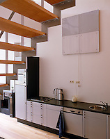 The installation of a central staircase unites kitchen, dining and work areas with the kitchen orientated along one wall