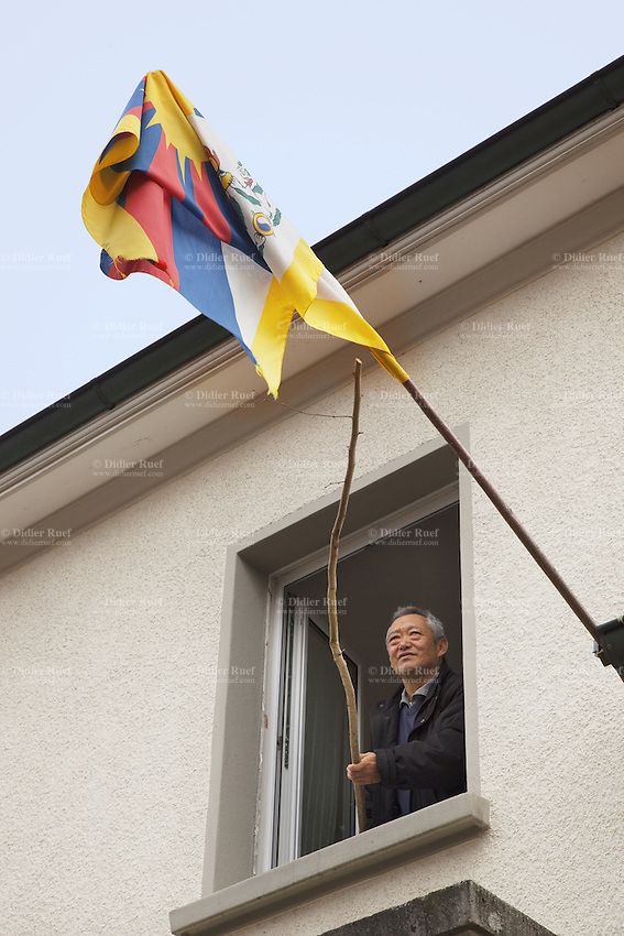 """Switzerland. Canton Bern. Muri. Thubten Purang at home with a tibetan flag. The swiss tibetan man is an Aeschimann's child who arrived 50 years ago in Switzerland to receive custody on a private initiative by an influential Swiss industrialist, Charles Aeschimann. In 1962, Charles Aeschimann agreed with the Dalai Lama to take 200 children and place them in Swiss foster homes and give them a chance for a better life and a good education. Most of the children still had parents in exile or in Tibet, just a few were orphans. The Tibetan flag, also known as the """"snow lion flag"""" and the 'Free Tibet flag', was a flag of the military of Tibet, introduced by the 13th Dalai Lama in 1912 and used for the same capacity until 1959. Designed with the help of a Japanese priest, it reflects the design motif of the Japanese military's Rising Sun Flag. Since the 1960s, it is used a symbol of the Tibetan independence movement. 24.02.2015 © 2015 Didier Ruef"""