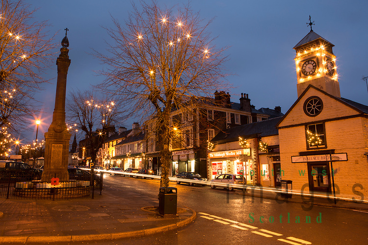 Moffat town centre Christmas lights decorations along the shops and in the trees on High Street at dusk