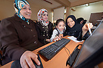 Iraqi refugee women learn computer skills, with help from one of their daughters, in a center for Iraqi refugees in Zarqa, Jordan. The center is supported by International Orthodox Christian Charities, a member of the ACT Alliance...