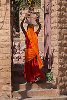 "Women carry a heavy load. Jodhpur Rajasthan India.J The city is known as the ""Sun City"" for the bright, sunny weather it enjoys all the year round. It is also referred to as the ""Blue City"" due to the vivid blue-painted houses around the Mehrangarh Fort. The old city circles the fort and is bounded by a wall with several gates."