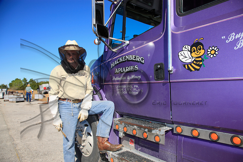 Dave Hackenberg, here at his apiary before the departure of the hives, directs the truck drivers by telephone. During fifteen days, his 2500 hives will set off in different convoys for California. Three days of traveling where anything can happen.