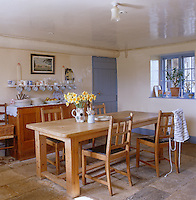 A table and early 20th centry chairs from Heal's sit in the centre of this rustic stone-flagged kitchen