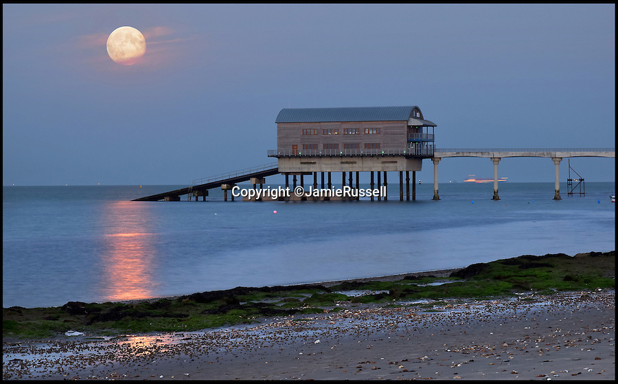 BNPS.co.uk (01202 558833)<br /> Pic: JamieRussell/BNPS<br /> <br /> ***Please Use Full Byline***<br /> <br /> The Supermoon can be seen over Bembridge Lifeboat Station.<br /> <br /> Stunning photographs have revealed a turbulent side to the normally genteel Isle of Wight.<br /> <br /> The seemingly benign south coast holiday destination has been catalogued over a stormy year by local photographer Jamie Russell, and his astonishing pictures reveal the dramatic changes in weather that roll across the UK in just 12 months.<br /> <br /> Lightning storms, ice, floods, gales and blizzards have all been captured by the intrepid photographer who frequently got up in the middle of the night to capture the climatic chaos.<br /> <br /> Looking at these pictures prospective holidaymakers could be forgiven for thinking twice about a gentle staycation on the south coast island.