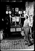View of a Telluride shopkeeper posing in front of his wares.<br /> Telluride, CO  Taken by Lee, Russell