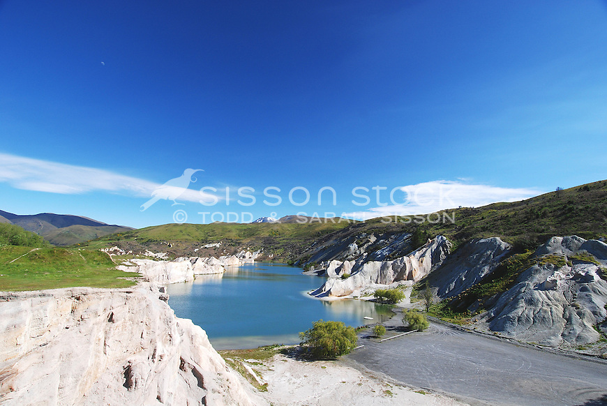 The Blue Lake at St Bathans in Central Otago, New Zealand on a sunny summer's day. The picturesque and beautiful lake was actually created by gold miners who used sluice guns to convert what was once Kildare hill into  a lake!