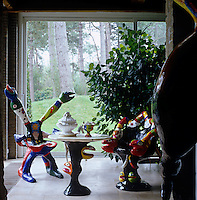 An imaginative table and chairs created by sculptor Niki de Saint Phalle are placed beside a sliding door which leads into the garden