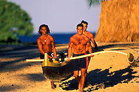 3 young men getting ready to workout in their outrigger canoe in the blue ocean waters off the Big Island of Hawaii