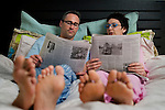 Mature couple reading newspaper, relaxing on bed