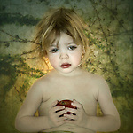 A young girl with blonde hair holding a red apple