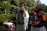 Tigist, second from left,HIV positive prays in an orthodox church where she can drink holy water that is belived by her family to heal from the virus in Addis Ababa, Ethiopia on Sunday July 16 2006.. Ethiopia is one of the countries most affected by HIV/AIDS. Of its population of 77 million, three million are HIV-positive, according to government statistics. Every day sees 1,000 new infections. A million children under 14 have lost one or both parents to AIDS, and 200,000 children are living with AIDS. That makes Ethiopia the country with the most HIV-positive children.