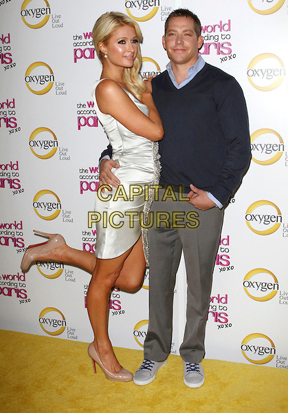 "PARIS HILTON & CY WAITS  .""The World According To Paris"" Series Premiere Party  Held At The Roosevelt Hotel, Hollywood, California, USA, .17th May 2011..full length sleeveless dress beaded  tanned fake tan beige nude shoes   silver hand on hip couple trousers grey gray blue shirt navy sweater jumper standing on one leg foot .CAP/ADM/KB.©Kevan Brooks/AdMedia/Capital Pictures."
