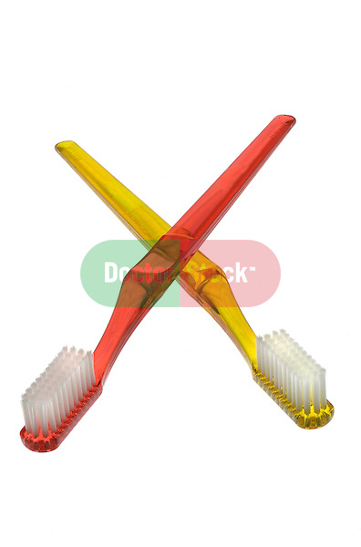 two toothbrushes crossed in X formation on shadowless white background