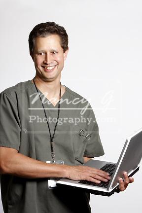 A Hawaiian ethnic man in scrubs using a laptop computer