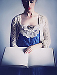 A woman in a vintage gown with a cameo, dark hair and eyes closed, holding a large book / diary