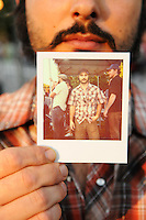 "Sam Yoder of Seattle holds a Polaroid photo depicting the outfit he wore to the 2011 Bumbershoot music and arts festival in Seattle Center on Monday, September 5, 2011. Yoder said comfort was his primary concern when choosing clothing. ""And it's obvious I like plaid,"" he said."