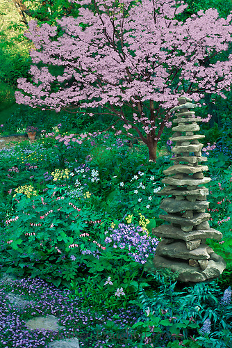 Spring shade garden with blooming dogwood, Conus florida, and a handbuilt rock cairn as garden art