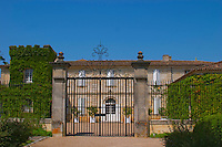 A black iron gate and main chateau building at Chateau Canon Saint Emilion Bordeaux Gironde Aquitaine France