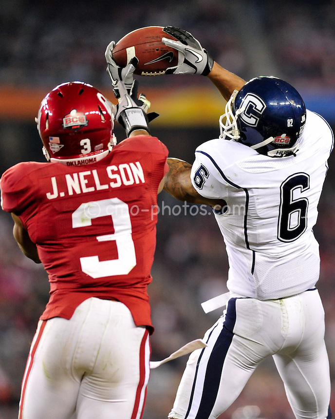 Jan 1, 2011; Glendale, AZ, USA; Connecticut Huskies wide receiver Kashif Moore (82) and Oklahoma Sooners defensive back Jonathan Nelson (3) both go up for a pass in the 4th quarter of the 2011 Fiesta Bowl at University of Phoenix Stadium.  The ball would fall incomplete and the Sooners won the game 48-20.