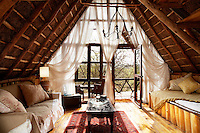 The living room of a boutique style luxurious wooden treehouse, made entirely of wood and grass. The interior has a rustic feel, with the talents of regional artists adding many of the finishing touches for example the carved low table and the chest are from Lamu. A door leads to a terrace area giving views to the Ngong hills.