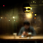 A young man sitting in a Starbucks window that is steamed over from the winter cold.