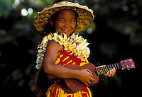 Young girl with yellow plumeria lei strums the ukelele.