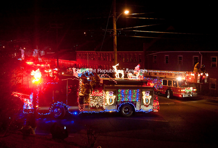 WINSTED, CT--- -121915JS05--Decorated fire trucks turn onto Lake Street from Meador Street in Winsted as they begin the 11th annual Winsted Fire Department &quot;Gator&quot; Christmas Parade on Saturday. The parade continues to honor the tradition of former firefighter Gaeton &quot;Gator&quot; Gangi who started the parade in 2004 as a community Christmas parade. <br /> Jim Shannon Republican-American