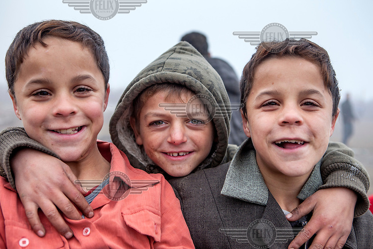 A boy stands between a pair of twin brothers in the Roma settlement located in 'Budulovskej Street'.