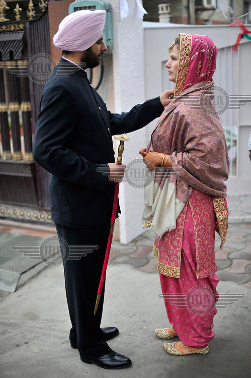 British/Punjabi couple Lindsay and Navneet Singh wait to be taken to their wedding ceremony at a gurdwara in Amritsar.