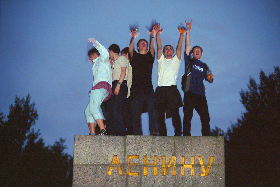 Saint Petersburg, Russia, June 2002..White Night ravers - dancers at 2 am on a plinth which formerly held a statue of Lenin, at the Leningradskii Subottnik all night rave. The mid-summer White Nights period when the sun sets only briefly is a time of festivals, entertainment and walks along the Neva River to watch the city bridges raise for shipping..