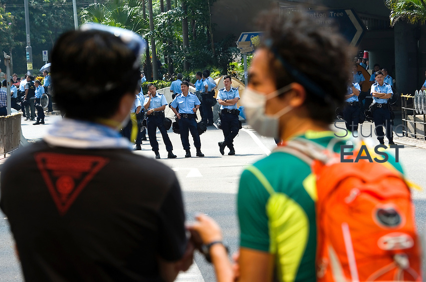 HONG KONG - OCTOBER 14: Police officers and pro-democracy 'Occupy Central' protesters have reached a face-off at a barricade set by protesters on Cotton Tree Drive, in Admirality on October 14, 2014 in Hong Kong. In the morning of October 14, police removed barricades and re-opened Queensway lanes for traffic. A third week of civil disobedience movements continues in response to China's decision to allow only Beijing-vetted candidates to stand in the city's 2017 election for the top civil position of chief executive. Protestors are calling for open elections and the resignation of Hong Kong's Chief Executive Leung Chun-ying. (Photo by Lucas Schifres/Getty Images)