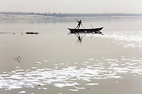 A fisherman pushes his boat along the Ganges River. Waste water in the foreground from nearby tanneries has contributed to the severe degradation of local water resources near the city of Kanpur. The city is notorious for having some of the country's worst water pollution which is created by the local leathery tannery industry.