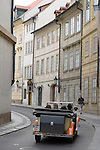 An antique tour guide car drives down a street in Prague, Czech Republic.
