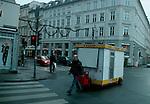 A vendor moves his hot dog cart through the Vesgterbro neighborhood of Copenhagen, Denmark