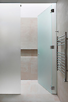 A modern tiled bathroom with a opaque glass door leading to a wet room. A chrome towel rail radiator is affixed to one wall.