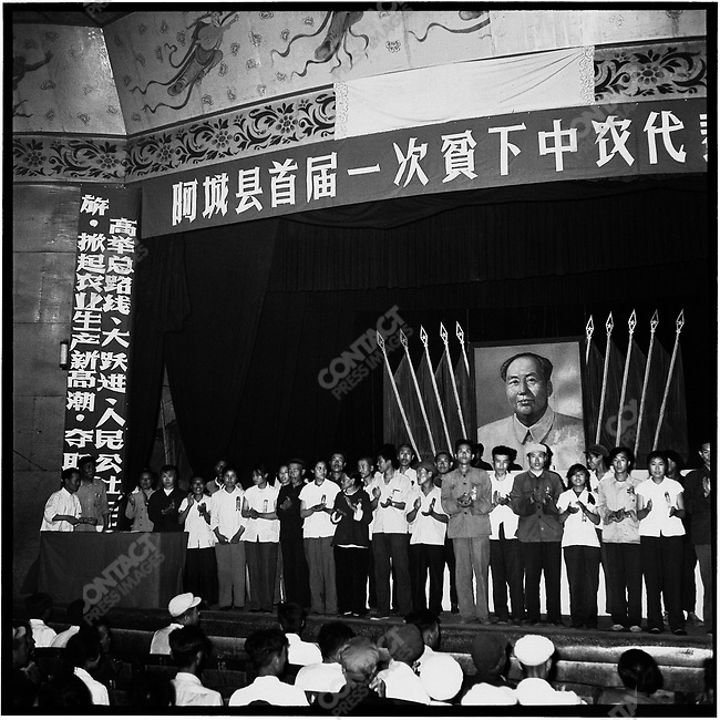 "At the end of a one-day conference, the newly elected leaders of the country's Poor and Lower Middle Peasants Association gather on the stage of the local theater. Banners encourage the attendees to ""lean from Da Zhai [a model production brigade]. To emulate Heilongjiang's model commune Tai Ping, and to work hard."" Acheng, Acheng county, 12 July 1965"