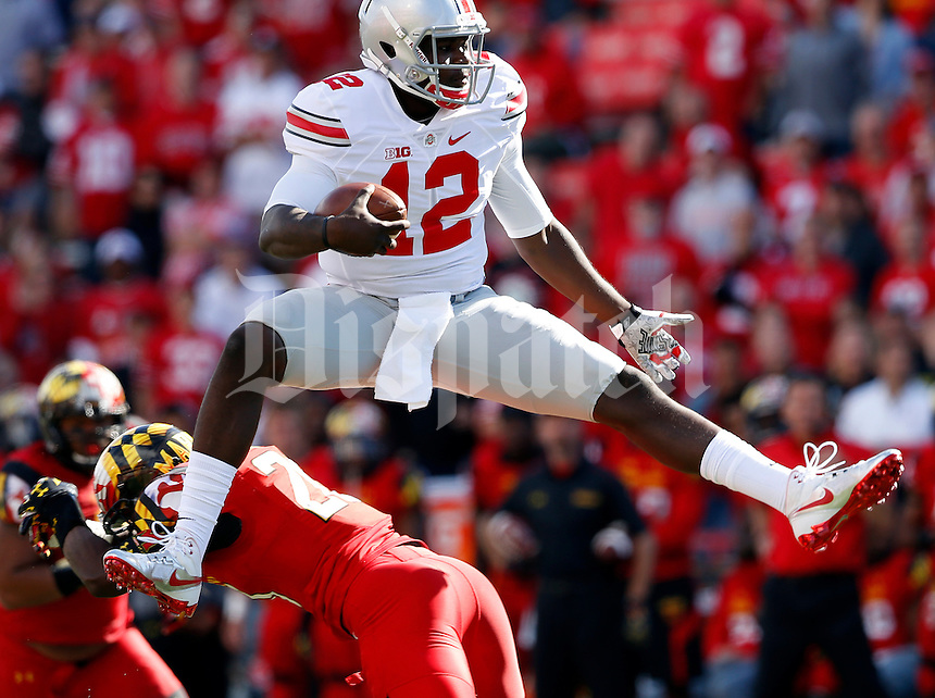 Ohio State Buckeyes quarterback Cardale Jones (12) leaps over Maryland Terrapins defensive back Anthony Nixon (20) during the fourth quarter of the NCAA football game at Byrd Stadium in College Park, Maryland on Oct. 4, 2014. (Adam Cairns / The Columbus Dispatch)
