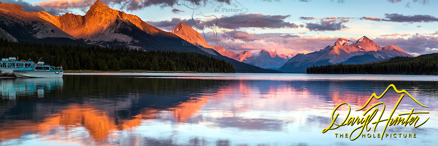 Maligne Lake Sunset Panorama, the Queen Elizabeth Range reflecting in the calm waters of the lake. <br />