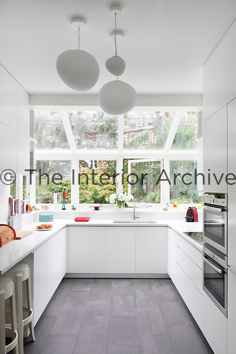 A modern galley kitchen with white units and grey painted floorboards in an extension with a skylight roof.