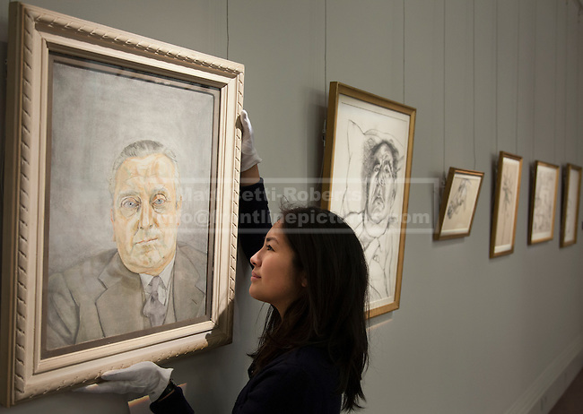 01/02/2012. LONDON, UK. A member of Sotherby's staff adjusts Lucian Frued's 'Portrait of a Man' as it hangs with  5 other pieces of his work at an auction of Impressionist and Modern Art held on the 15th of February 2012. The painting, never seen before in public, depicts Bernard Walsh, who's Soho restaurant was frequented by artists, including Freud throughout the 1950's and 60's, and is estimated to raise £1,5000,000-2,000,000. Photo credit: Matt Cetti-Roberts