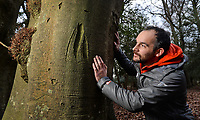 BNPS.co.uk (01202 558833)<br /> Pic: ZacharyCulpin/BNPS<br /> <br /> Pictured: Lawrence Shaw, archaeologist at the New Forest NPA with 'Kings Mark' graffiti. One of the most common marks is the 'King's Mark', a broad arrow head used to identify trees reserved for building Royal Navy ships in the 18th and early 19th century. <br /> <br /> Fascinating ancient graffiti which was carved into the trees of the New Forest centuries ago is being formally recorded for the first time.Initials, dates, pictures, poems and royal marks which vary in size from 4ins to 2ft can be found throughout the national park in Hampshire.There are also various examples on display of concentric circles, known as 'witches marks', which were carved to ward off evil spirits.In total, hundreds of examples of 'tree graffiti' are being documented in a new database set up by the New Forest National Park Authority.