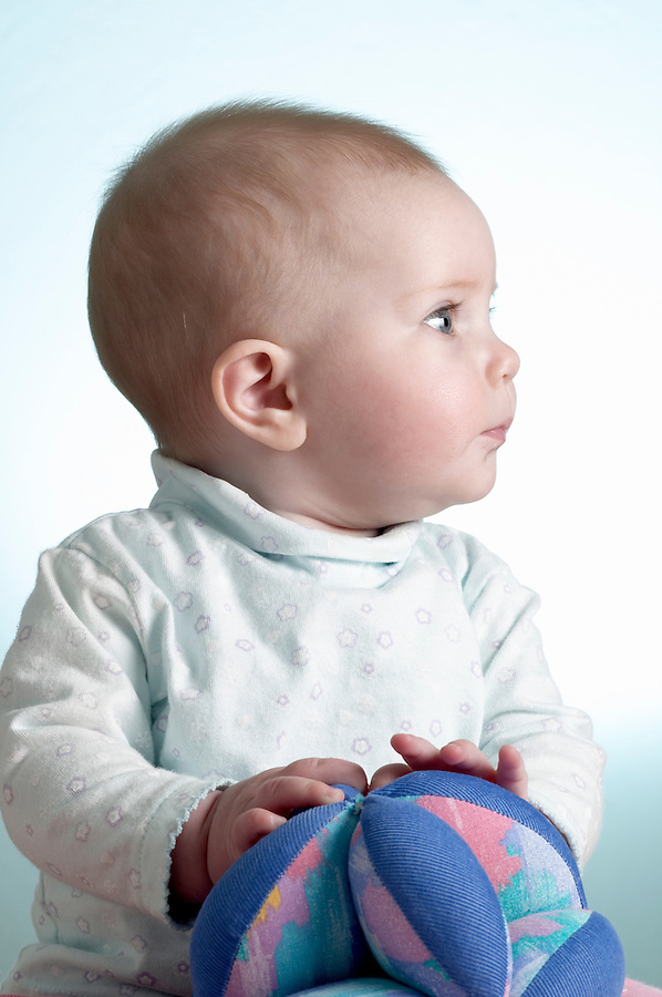 Portrait of 6 month old baby girl sitting with soft toy ball