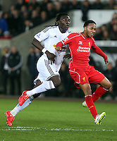 SWANSEA, WALES - MARCH 16: L-R Bafetimbi Gomis of Swansea is held back by Raheem Sterling of Liverpool during the Premier League match between Swansea City and Liverpool at the Liberty Stadium on March 16, 2015 in Swansea, Wales