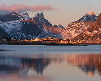 Morning winter light shines over small village with mountains of Moskenesøy in the background, Lofoten Islands, Norway