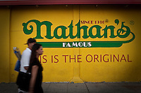 A man and a woman walk by a Nathan's Famous advertising mural on Coney Island in New York city borough of Brooklyn, Sunday July 31, 2011. Nathan's Famous (NASDAQ: NATH) is a company that operates a chain of U.S.-based fast food restaurants specializing in hot dogs.