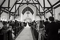 Black and white view of ceremony from the rear of the church.