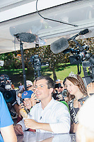 South Bend mayor and Democratic presidential candidate Pete Buttigieg orders a pork loin on a stick at the Iowa State Fair in Des Moines, Iowa, on Tues., Aug. 13, 2019.