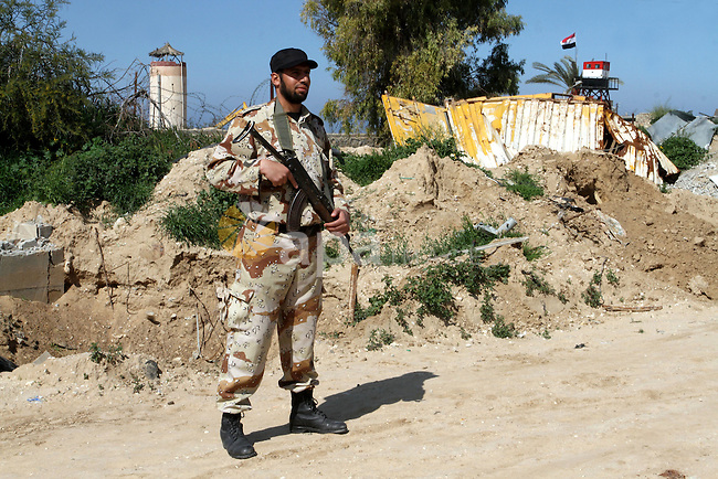 A member of Palestinian security forces stands guard on the border between Egypt and southern Gaza Strip, in Rafah on March 5, 2015. Gaza's border crossings will be reopened once control of them is handed over to the Palestinian Authority, Egypt's Ambassador to the Palestinian Authority (PA) Wael Attia said. Photo by Abed Rahim Khatib