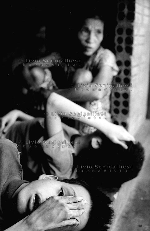 Cam Nghia / provincia di Quang Tri / Vietnam.<br /> La guerra del Vietnam si è conclusa nel 1975 ma i fratelli Nguyen, nati dopo la fine del conflitto, ne sono ancora vittime. La malattia mentale da cui sono afflitti e le deformità fisiche sono conseguenza dell'Agente Arancio, defoliante dall'alto contenuto di diossina che gli aerei USA hanno nebulizzato tra il 1961 e il 1971 sul delta del Mekong e nella zona degli Altopiani Centrali ai confini col Laos.<br /> Foto Livio Senigalliesi.<br /> Cam Nghia / Quang Tri / Vietnam.<br /> In the picture Nguyen Le Thi Mit (58) and her sons Van Truong (16) and Van Lan (22).Vietnam war ended in 1975 but the Nguyen brothers are its victims even though born after the end of the conflict. The mental disease and the physical deformities they suffer from are the consequences of the Agent Orange, the herbicide containing a high concentration of dioxine which the US planes sprayed between 1961 and 1971 on the Mekong delta and in the area of the Central Tableland bordering with Laos.<br /> Photo Livio Senigalliesi
